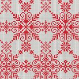 Teste padrão sem emenda feito malha dos flocos de neve brancos em um fundo vermelho Foto de Stock Royalty Free