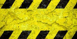 Teste padr?o amarelo e preto do sinal de advert?ncia do perigo das listras com ?rea amarela sobre a fachada concreta da parede do imagem de stock royalty free
