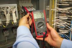 Tester i hand av den elektriska teknikern i automationpanel Justera den elektriska panelen med multimeteren Royaltyfri Foto