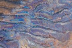 Testes padrões coloridos do óleo na areia da praia Testes padrões da poluição na costa do mar Báltico Foto de Stock