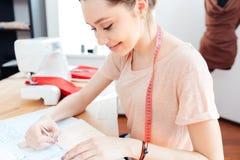Testes padrões felizes do assento e do desenho da costureira da mulher no caderno Fotografia de Stock