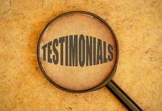 Testimonials. Magnifying glass over the word testimonials Royalty Free Stock Images