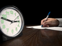 Testing. Clock with a man doing written test in the background, low key, useful for job application.education and other testing related themes Royalty Free Stock Photo