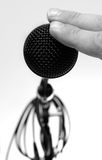 Testing, Is this On?. Fingers tap a black microphone Stock Photography
