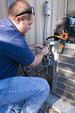 Testing AC Unit. Repair man testing air conditioner unit with voltage metering equipment Royalty Free Stock Images