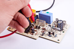 Testing a board. Hand with testing tips of multimeter on a circuit-board Stock Images