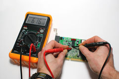 Testing a computer modem with digital multimeter Royalty Free Stock Photos