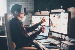 Testing games. Young man wearing virtual reality headset and gesturing while sitting at his desk in creative office Royalty Free Stock Photos