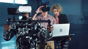 Testing gimbal camera stabilizer with VR headsed. Young people testing camera gyro stabilizer gimbal with virtual reality headset on, looking around. Men and Stock Photography