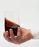 Testing red wine. In stemless glass on sommelier hand isolated on white background. Drink red wine Stock Images