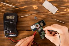 Testing and repair the chip for service by means of a tester and a set of electronics engineer. Radioelectronic Testing Set for soldering wire and shrink Stock Photography