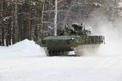 Testing of the upgraded infantry fighting vehicle BMP-2 in winter conditions. BMP-2 at movement on the March with maximum speed in the winter forest, armament Stock Photo