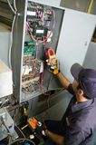 Testing voltage. Worker testing voltage on a buildings environmental control box Royalty Free Stock Images