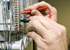 Testing Voltage. A man testing the voltage on a telephone punch block Royalty Free Stock Image