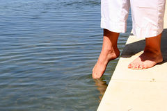 Testing the Water. Woman putting her toes in the water to see if it is warm yet Royalty Free Stock Photo