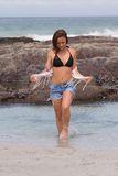Testing The Water. Beautiful beach babe in bikini and shorts dipping her toes in the sea Stock Images