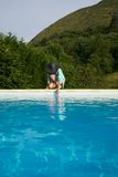 Testing water on swimming pool border Stock Image
