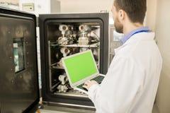 Testingenieur in laboratoriumlaag het kalibreren meetinstrumenten stock fotografie