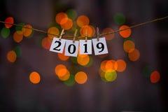 Testo del buon anno 2019 sulle carte con le mollette da bucato con il bokeh della ghirlanda su fondo Anno di maiale immagine stock libera da diritti