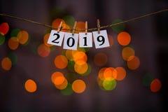 Testo del buon anno 2019 sulle carte con le mollette da bucato con il bokeh della ghirlanda su fondo Anno di maiale immagini stock