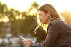 Testo della lettura della donna in uno Smart Phone al tramonto Immagine Stock