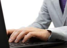 Testo di battitura a macchina dell'uomo d'affari su una tastiera del computer portatile Immagine Stock