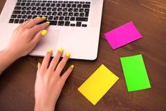 Testo di battitura a macchina della donna con le mani ed il manicure al neon sulla tastiera del computer portatile fotografia stock libera da diritti
