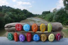 Testo di buon compleanno con le pietre colorate oltre due pezzi di legno e sfondo naturale fotografie stock