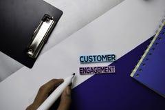 Testo di impegno del cliente sulle note appiccicose con il concetto della scrivania di colore fotografie stock