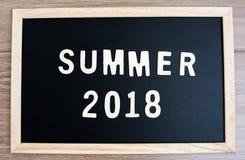 testo di legno di parola di estate e 2018 buoni anni sulla lavagna e Fotografia Stock Libera da Diritti