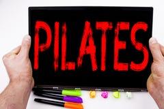 Testo di Pilates scritto sulla compressa, computer nell'ufficio con l'indicatore, penna, cancelleria Concetto di affari per l'all Fotografie Stock