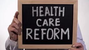 Testo di riforma di sanità sulla lavagna in mani di medico, politica del governo statale fotografia stock libera da diritti