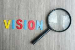 Testo di VISIONE sulla nota gialla con carta e la lente d'ingrandimento sbriciolate sul fondo di legno della tavola SEO, idea, so fotografie stock