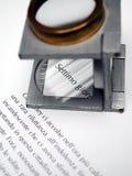Testo e lente di ingrandimento Fotografia Stock