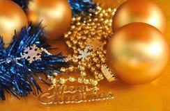 Testo ed ornamenti del metallo di Buon Natale sul fondo dell'oro Fotografia Stock