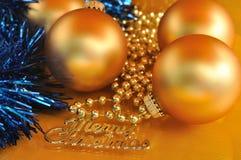 Testo ed ornamenti del metallo di Buon Natale sul fondo dell'oro Fotografia Stock Libera da Diritti