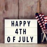 Testo felice il quarto luglio e bandiere americane Fotografia Stock Libera da Diritti