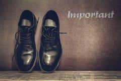 Testo importante sulle scarpe marroni di lavoro e del bordo sul pavimento di legno fotografie stock libere da diritti