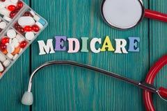 Testo & x22; Medicare& x22; delle lettere, dello stetoscopio e delle pillole di legno colorati immagini stock libere da diritti
