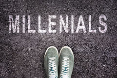 Testo Millennials scritto su asfalto con le scarpe Fotografia Stock Libera da Diritti