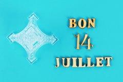 Testo nel buon 14 luglio francese Miniatura della torre Eiffel su un fondo blu Il concetto della festa il giorno del bloccaggio Immagine Stock