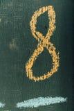 Testo numero otto sulla lavagna Numero otto scritto il gesso della mano a bordo Immagine Stock
