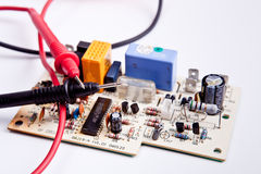 Testtips with board. Testing  tips of multimeter on circuit-board Royalty Free Stock Photos