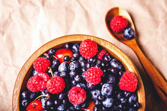 Testy fresh berries. In wooden plate and spoon Stock Photos