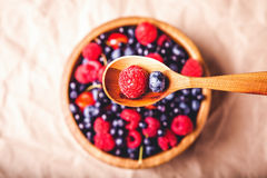 Testy fresh berries. In wooden plate and spoon Stock Image