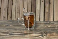 Tetång i den glass koppen med te på en trätabell arkivbild