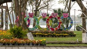Tet Year of the Pig display with yellow and pink flowers, located in Hue along the Parfume River. Pictured is a Tet Year of the Pig display with peach flowers stock photos