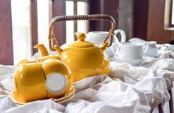 Tetera amarilla con una taza y un platillo Fotografía de archivo