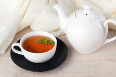 Tetera blanca con una taza de té y de menta Foto de archivo