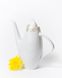 Tetera blanca de cerámica checa y flor amarilla en el fondo blanco Foto de archivo